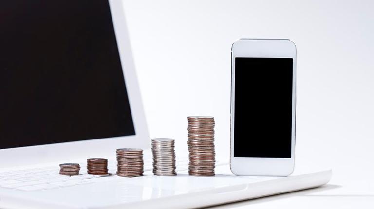 노트북 위에 세워진 동전탑과 휴대전화