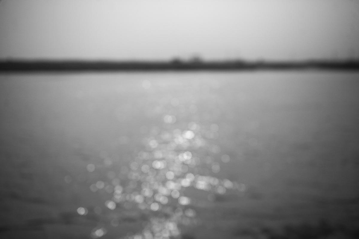 완도앞바다를 포커싱을 흐리게 만들어 촬영된 사진으로 수면에 반사된 태양빛이 빛망울처럼 동그랗게 나타나있고 그 너머에는 육지로보이는 지평선이 보인다.
