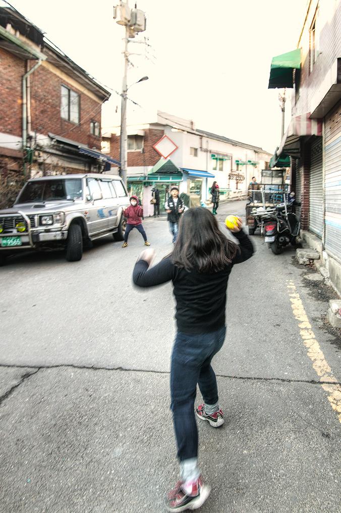 이제는 보기힘든 골목길에서 공놀이하는 아이들 사진-한 여자아이가 공을 던지려 포즈를 취하고 조금 떨어진곳에서 남자아이 둘이 그 공을 받을 준비를 하고있다.